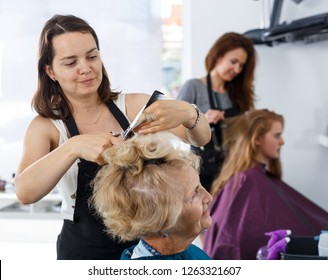 Skilled woman hairdresser making hairstyle for elderly female client in hair studio