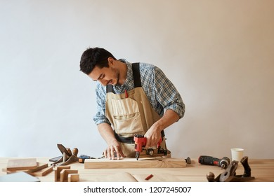 Skilled woodworker and small business owner working in his woodwork workshop, using drill, making hole through a wooden plank, hobby concept.