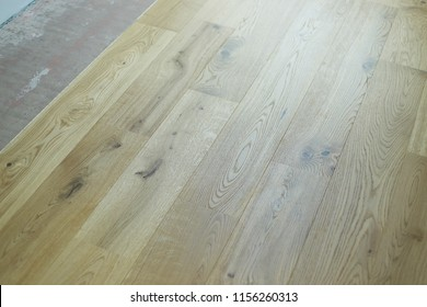 Skilled worker during the installation of pre-finished interlocking parquet. Installation of oak colored parquet.Laying with brown glue on an existing floor.