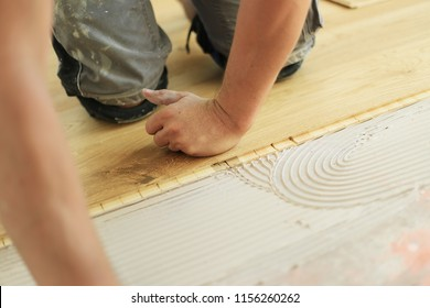 Skilled worker to lay parquet. Installation of oak colored parquet.a man on a building site. parquet