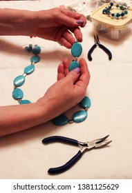 a skilled worker in the process of making beautiful turquoise beads for women, on a light background next to tools for needlework, a container for storing bijouterie, bright beads