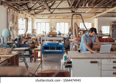 Skilled young craftsman standing at a workbench in his large carpentry studio full of woodworking equipment using a laptop