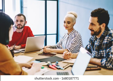 Skilled young male and female student working in group prepare project together discussing and using technology, smiling crew of multiracial colleagues sitting at meeting table share ideas for startup