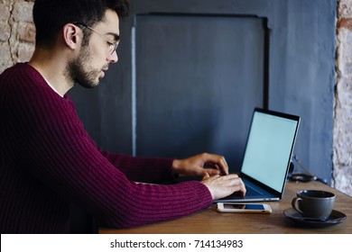 Skilled young IT professional writing email for customer during programming new useful web application on laptop computer with blank screen for your promotional content while working remotely