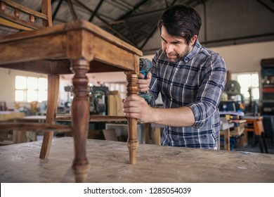 Skilled young woodworker using a drill on a wooden chair on a workbench while working alone in his large woodworking shop