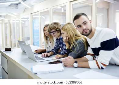 Skilled,young IT programmers brainstorming while creating code for new outsourcing smartphone application via modern laptop computer connected to fast 4G wifi, working together in coworking space