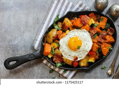 Skillet Breakfast Hash with potatoes bacon  peppers sweet potatoes cheese Zucchini  and fried egg, top view with copy space