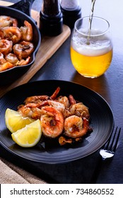 Skillet roasted jumbo shrimp on a black plate. Beer pouring into a glass.
