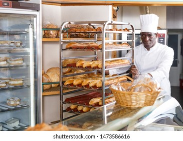 Skillful African American baker working in small bakery, carrying fresh baked baguettes on rack