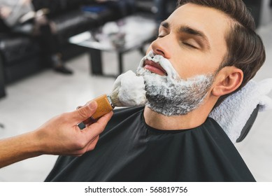 Skillful beautician preparing to shave stubble