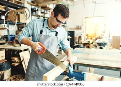 Skillful carpenter sawing a piece of wood placed in workbench vice with hand saw in his workshop