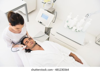 Skillful cosmetologist massaging male face with equipment