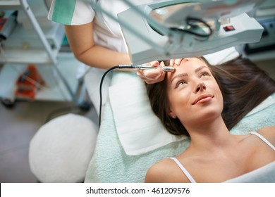 Skillful cosmetologist is undergoing microdermabrasion of skin on female face