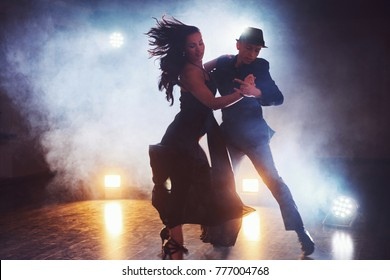 Skillful dancers performing in the dark room under the concert light and smoke. Sensual couple performing an artistic and emotional contemporary dance.