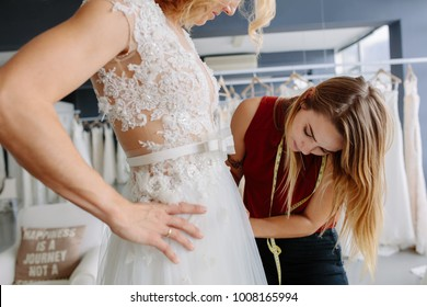 Skillful dress designer fitting wedding gown to woman in her boutique. Woman making adjustments to bridal gown in fashion designer studio.