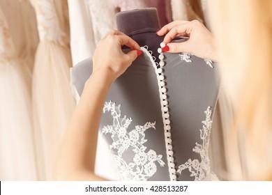 Skillful female dressmaking adjusting buttons on clothing