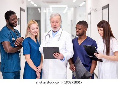 Skillful general student practitioners discussing human health with senior doctor, having conversation with experienced professional medical worker, in hospital