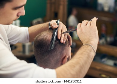 Skillful hairdresser's hands cutting off male hair with professional tools in barbershop. Short haircut for men with scissors and comb helping. Masterful hands in workflow. Blurred background.