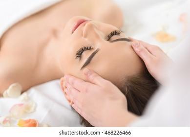 Skillful masseuse massaging human head