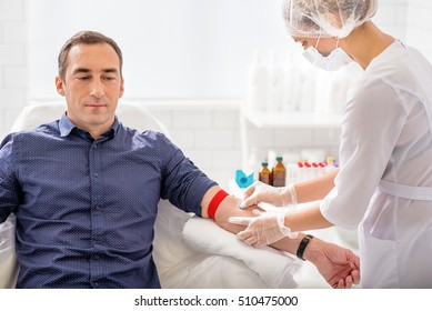 Skillful nurse is doing blood test for man in clinic