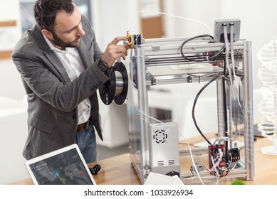 Skillful preparation. Dark-haired young engineer inserting filament into the extruder of a 3D printer, preparing it for work thoroughly