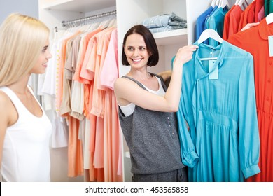 Skillful saleswoman advising girl in boutique