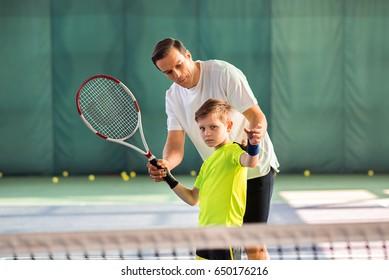 Skillful trainer teaching kid holding racquet