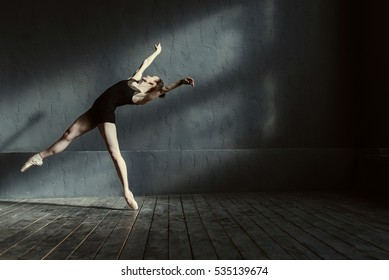 Skillful young ballet dancer acting in the black colored room