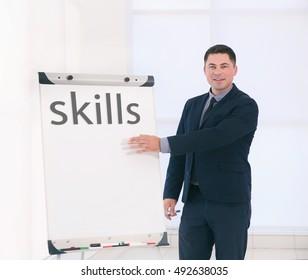 Skills. Business trainer giving presentation on whiteboard