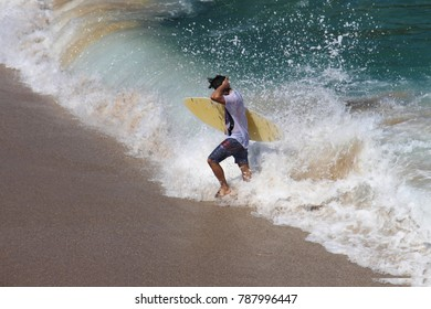 Skim boarder coming in from the surf after skimming on his board - waves crashing around him