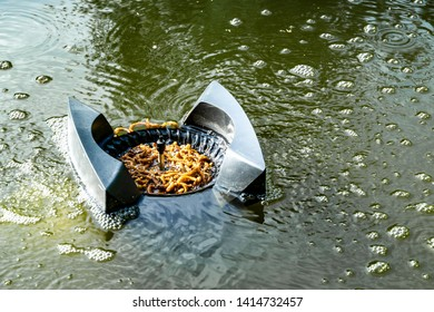 Skimmer floats on surface of water and collects leaves, dirt and other foreign objects from surface . Close-up. Skimmer filled with plants trapped in water.