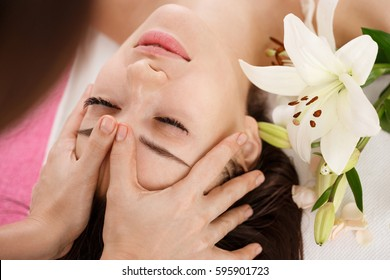 Skin and body care. Young woman getting face massage. Facial beuty