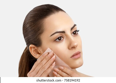 Skin Care. Beauty Face. Woman removing oil from face using blotting papers. Closeup Portrait Of Beautiful Healthy Girl With Nude Makeup. Perfect Soft Skin With Oil Absorbing Tissue Sheets.