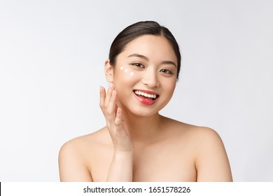 Skin care beauty woman. Beauty woman smiling applying cream. Beauty portrait of beautiful Asian Caucasian female model isolated on white.