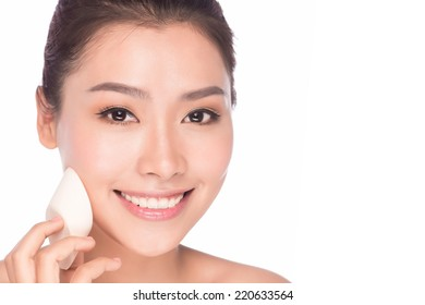 Skin care beauty woman. Beauty woman smiling applying cream. Beauty portrait of beautiful Asian female model isolated on light blue background looking at copy space.