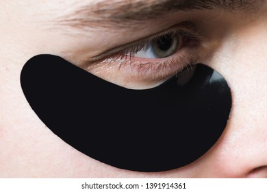 Skin care. Black pearl extract. Minimizes puffiness and reduce dark circles. Eye patches for men. Man with black eye patches close up. Metrosexual concept. Focused treatments for under eye area.