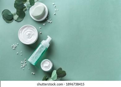 Soins de la peau, produits de soin du corps, feuilles d'eucalyptus, sel de mer sur fond vert, vue de dessus, espace pour copie. Spa et concept de soins de la peau naturels.