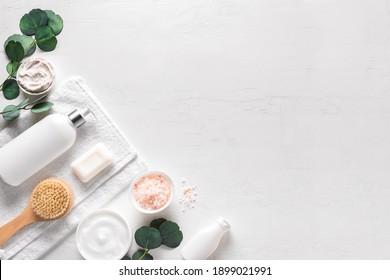 Soins de la peau, produits de traitement du corps et feuilles vertes sur fond blanc, vue de dessus, espace pour copie. La beauté naturelle et le concept de soin de la peau organique, la pose à plat.