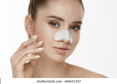 Skin Care. Closeup Of Beautiful Woman Beauty Face With White Patch, Pore Strip On Nose. Portrait Of Sexy Girl With Fresh Makeup Touching Clean Soft Pure Facial Skin With Hand. High Resolution