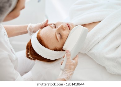 Skin Care Concept. Beautician hand with RF lifting medicine device boosting skin turgor to gorgeous female client with fresh and healthy skin, white coloures , medical sterility.