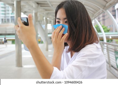 Skin care concept, Beautiful asian girl using oil remover paper on her face and looking at smartphone on street background