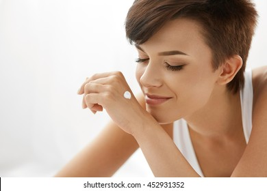 Skin Care Concept. Beautiful Woman With Hand Cream, Lotion On Her Hands. Closeup Portrait Of Happy Smiling Girl With Nude Makeup, Natural Manicure Smelling Cosmetic Cream On Soft Skin. Beauty Concept
