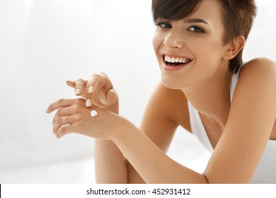 Skin Care Concept. Beautiful Woman With Hand Cream, Lotion On Her Hands. Closeup Portrait Of Happy Smiling Girl With Nude Makeup, Natural Manicure Applying Cosmetic Cream On Soft Skin. Beauty Concept