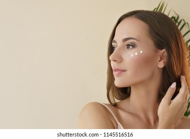 skin care concept. close up portrait of beautiful woman with cosmetic cream on face