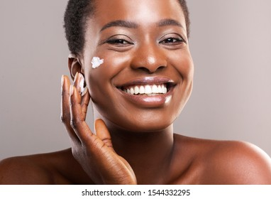 Skin Care Concept. Closeup Portrait Of Happy African American Woman Applying Moisturizing Cream on Face Over Grey Background