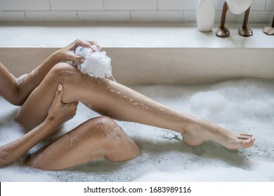 Skin care concept. Cropped view of young adult woman taking bath, lying in soap foam water, holding sponge in hand, washed leg