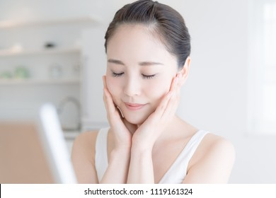 Skin care concept. Young asian woman checking her skin.