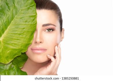 Hautpflege-Konzept mit einer jungen, schönen Frau, die ihr Gesicht perfekt berührt, während sie die Kamera hinter einem großen grünen Blatt betrachtet. Studioaufnahme, einzeln auf Weiß mit Kopienraum