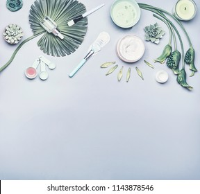 Skin care cosmetic and homemade facial mask background. Various serum, cream and gel cosmetics product with tropical leaves and flowers on gray background, top view with copy space. Beauty concept