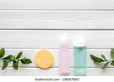 skin care cosmetics with facial tonic, mycelial water and sponge on white wooden background top view mockup